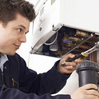 Plumber Working On Central Heating Boiler